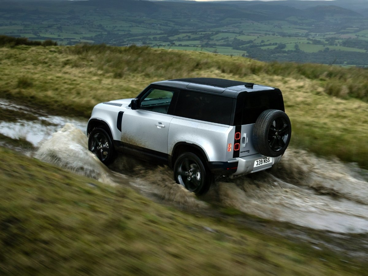 2021 Land Rover Defender 90 Silver Rear Quarter View Muddy Wet Trail