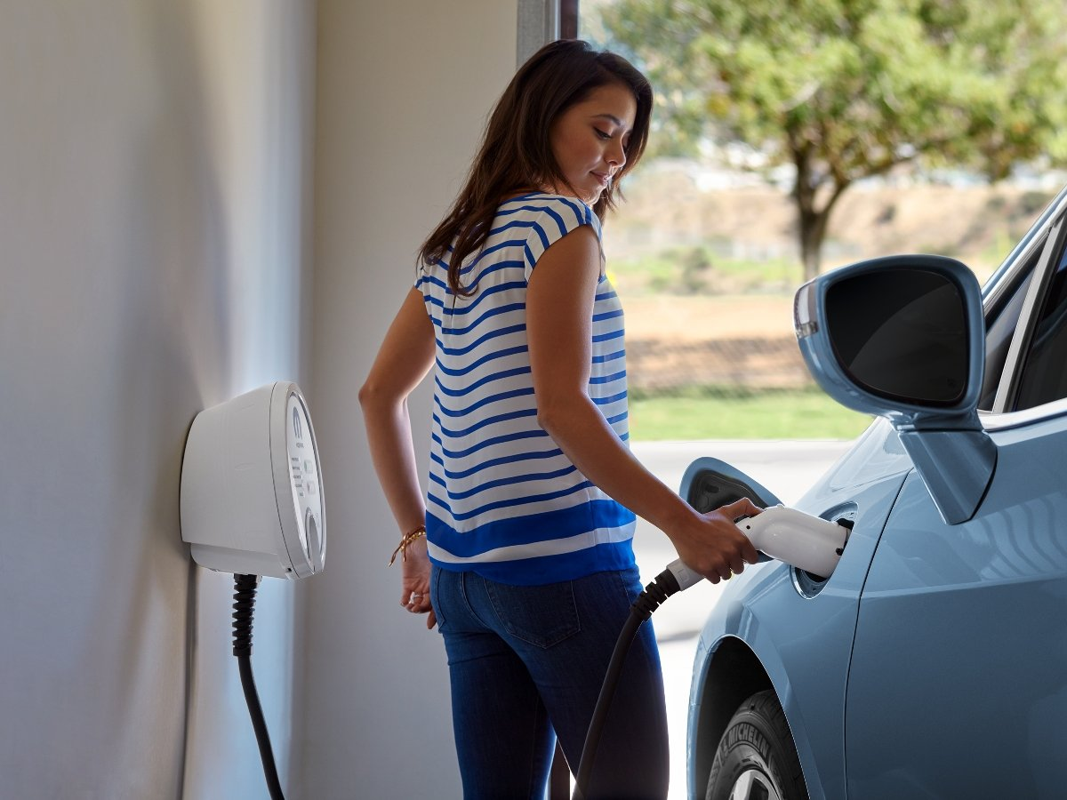 Woman Using Home Charging Station to Charge Electric Car